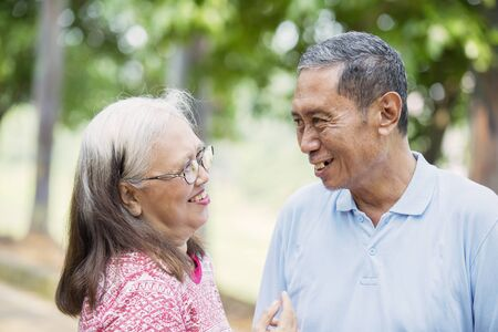 Picture of romantic old couple chatting together and standing in the park Stockfoto
