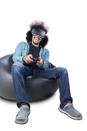 Portrait of curly hair man using virtual reality glasses and joystick for play video game, isolated on white background