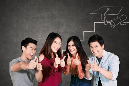 Group of happy college students showing thumbs up at the camera while standing with drawn of graduation cap on a chalkboard