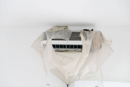 Image of dirty air conditioner blower fan and coil wrapped by plastic during cleaning service