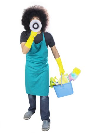 Afro male maid shouting at the camera with a loudspeaker while holding a bucket, isolated on white background