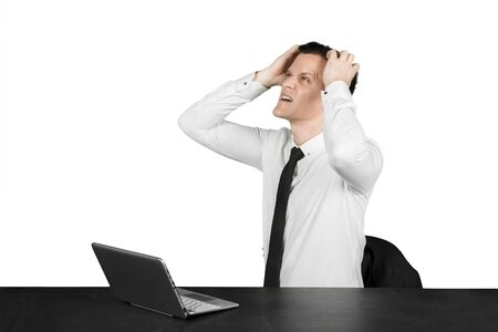 Caucasian male manager looks frustrated while working with a laptop on the desk, isolated on white background