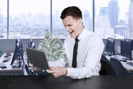 Image of young Caucasian businessman looking at money out of his laptop with happy expression in the office