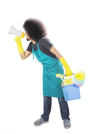Portrait of Afro male maid using a megaphone to shout while holding a bucket, isolated on white background