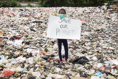 JAKARTA - Indonesia. May 27, 2019: Little girl showing a paper with text of Save Our Planet in while standing in the landfill