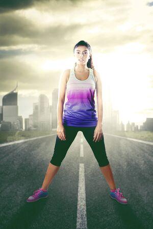 Jeune femme portant des vêtements de sport et debout dans la rue et lisant pour faire de l'exercice