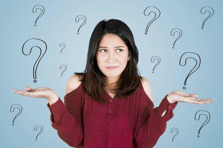 Bild einer jungen asiatischen Frau sieht verwirrt aus, während sie mit Fragezeichen steht Standard-Bild