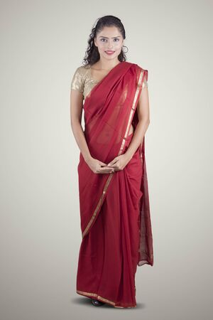 Full length of young Indian woman wearing a red saree and smiling at the camera. Shot in the studio, isolated on white background