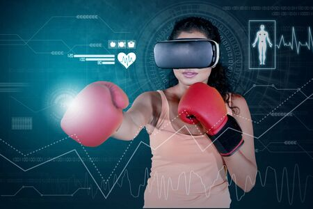 Young woman wearing boxing gloves and VR glasses while exercising with virtual simulation 版權商用圖片