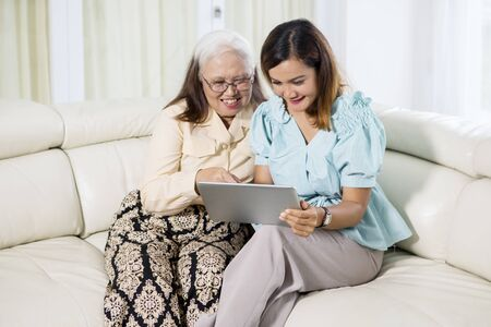 Young woman using a digital tablet with her mother while sitting together on the couch