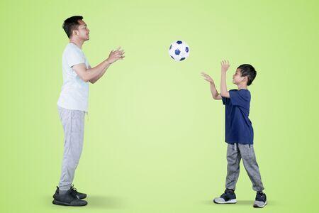 Foto van een kleine jongen die een voetbal naar zijn vader gooit terwijl hij samen in de studio speelt met groen scherm