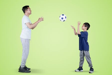 Picture of little boy throwing a soccer ball to his father while playing together in the studio with green screen