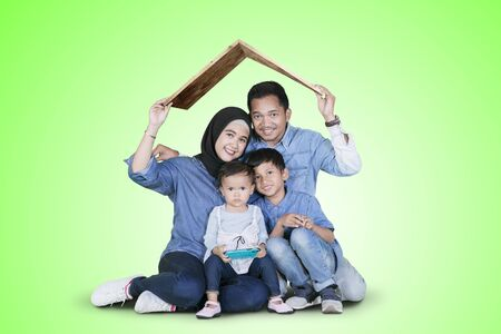 Smiling Muslim family holding a house roof symbol from cardboard over their heads while sitting in the studio with green screen Stockfoto