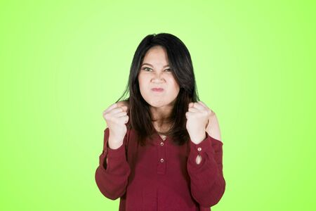 Picture of young angry woman clenching her fists with furious gesture in the studio. Shot in green screen Stock Photo