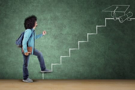 Étudiant afro-américain portant un livre et un sac en marchant dans l'escalier vers l'obtention du diplôme. Tourné en classe