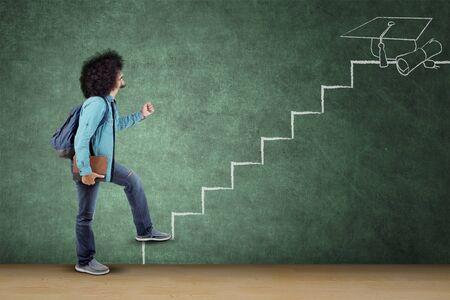 非洲男性大学生运载书和袋子,当走在梯度楼梯时。在教室里拍摄