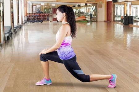 Side view of sporty woman doing warm-up before exercising in the fitness center