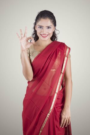 Attractive Indian woman showing OK hand gesture while wearing a red saree, isolated on white background Stock Photo