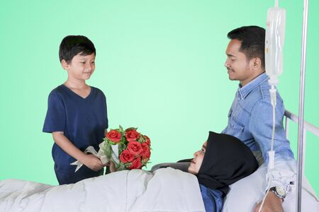Little boy and his father giving a bouquet to his sick mother in the studio with green screen Stock fotó