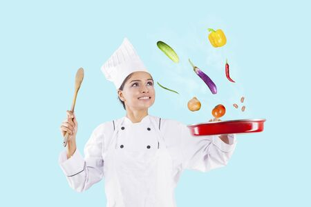 Happy female chef throwing food ingredients in a frying pan while cooking in the studio Imagens