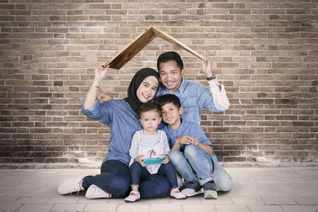 Smiling Muslim family holding a house roof symbol from cardboard over their heads while sitting with bricks wall background