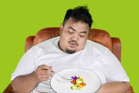 Fat man looks bored to eat a plate of healthy food on the sofa and sitting in the studio