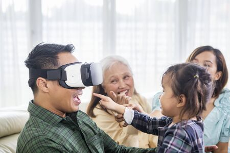 Close up of a happy young man wearing a VR headset with his family at home while sitting on the sofa 写真素材