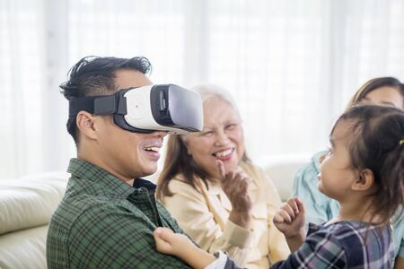 Young man wearing VR headset with his family at home while sitting on the sofa