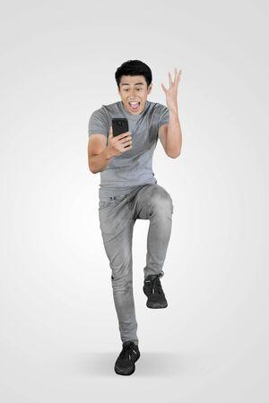 Der junge asiatische Mann sieht in voller Länge schockiert aus, während er im Studio ein Mobiltelefon benutzt