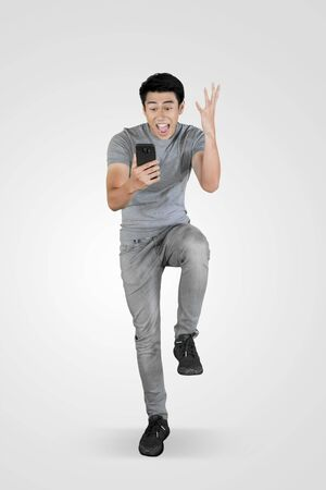 Full length of young Asian man looks shocked while using a mobile phone in the studio