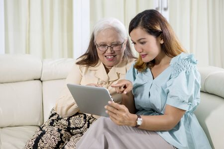 Picture of elderly woman using a digital tablet with her daughter while sitting together on the couch Stock Photo