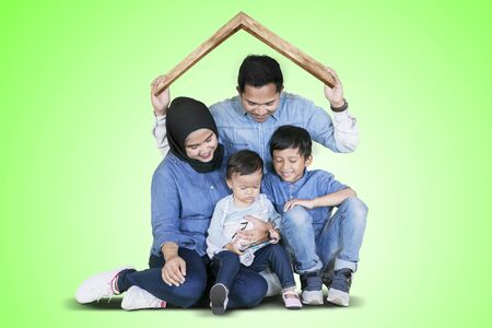 Muslim family holding a house roof symbol from cardboard over their heads while playing together in the studio with green screen Stockfoto