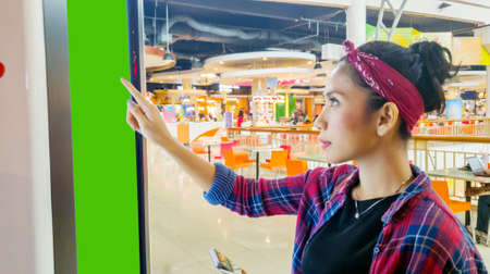 Asian woman touching blank screen while using a self-service kiosk in the mall Stock Photo