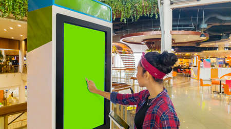 Young woman holding a digital tablet while touching a blank screen of self-ordering kiosk in the mall Stock Photo
