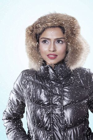 Picture of pensive woman wearing winter jacket while standing in the studio, isolated on white background