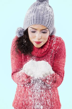 Attractive woman wearing red knitted sweater while blowing snow from her hands in the studio