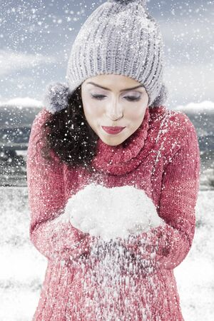Young woman wearing red knitted sweater while blowing snow from her hands