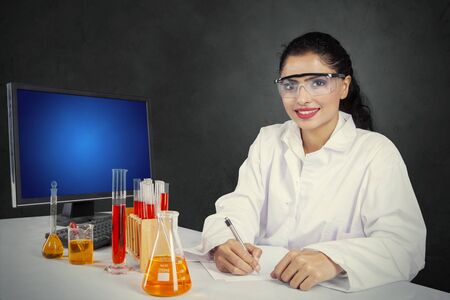 Beautiful female scientist smiling at the camera while sitting with test tubes in the studio Stock Photo