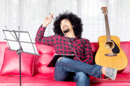 African musician thinks for composing a song at home while sitting on the couch