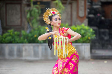 Attractive female Balinese dancer showing a dance while throwing frangipani flowers at outdoor 版權商用圖片