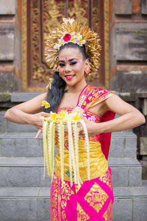 Beautiful balinese dancer smiling at the camera while holding frangipani flowers in the temple