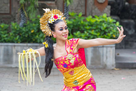 Female Pendet dancer showing a dance while carrying a bowl of flower petals at outdoor 版權商用圖片
