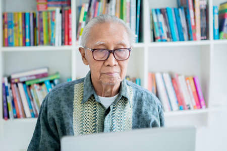 Senior man using a laptop computer while wearing glasses in the library with bookcase background