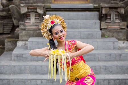 Young balinese dancer dancing while carrying frangipani flower in the temple