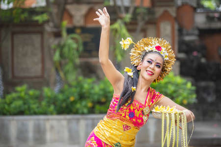 Beautiful female Balinese dancer showing a dance while throwing frangipani flowers at outdoor 版權商用圖片