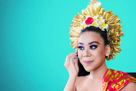 Balinese dancer using a sponge to apply foundation on her face in the studio