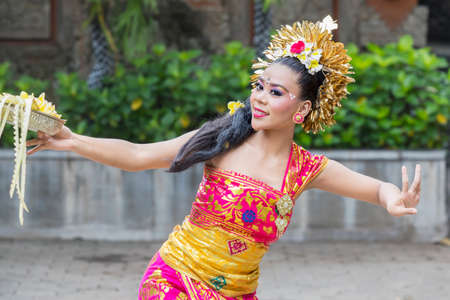 Beautiful Pendet dancer showing a dance while carrying a bowl of flower petals at outdoor