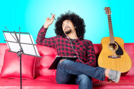 African musician thinks to composing a song while sitting on the couch. Shot in the studio