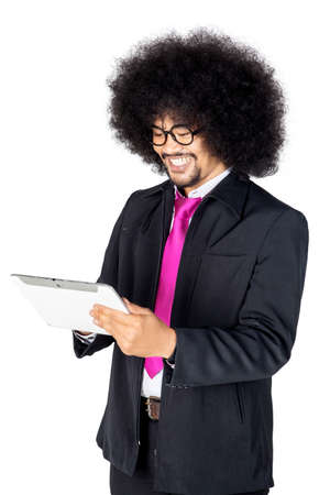 Curly hair businessman using a digital tablet with happy expression in the studio, isolated on white background Banco de Imagens