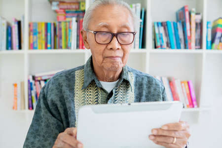 Elderly man using a digital tablet while wearing glasses in the library with bookcase background